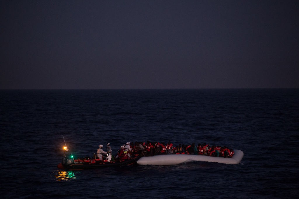 LAMPEDUSA, ITALY - JUNE 10: Refugees and migrants wait to be rescued in the early housr of the morning by crewmembers from the Migrant Offshore Aid Station (MOAS) Phoenix vessel on June 10, 2017 off Lampedusa, Italy. An estimated 230,000 refugees and migrants will arrive in Italy this year as numbers of refugees and migrants attempting the dangerous central mediterranean crossing from Libya to Italy continues to rise since the same time last year. So far this year more than 58,000 people have arrived in Italy and 1,569 people have died attempting the crossing. Libya continues to be the primary departure point for refugees and migrants taking the central mediterranean route to Sicily. In an attempt to slow the flow of migrants, Italy recently signed a deal with Libya, Chad and Niger outlining a plan to increase border controls and add new reception centers in the African nations, which are key transit points for migrants heading to Italy. MOAS is a Malta based NGO dedicated to providing professional search-and-rescue assistance to refugees and migrants in distress at sea. Since the start of the year MOAS have rescued and assisted more than 4000 people and are currently patrolling and running rescue operations in international waters off the coast of Libya. (Photo by Chris McGrath/Getty Images)