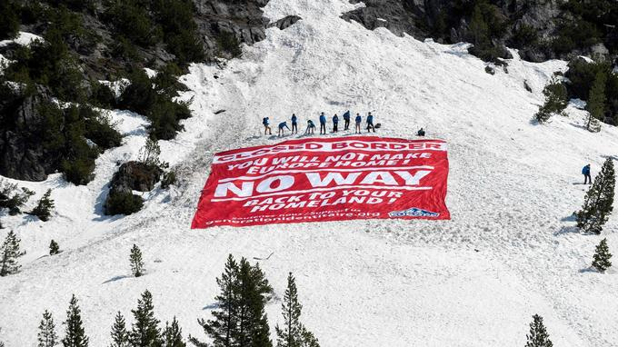 "TOPSHOT - Activists from the French far-right political movement Generation Identitaire (GI) and European anti-migrant group Defend Europe conduct an operation titled ""Mission Alpes"" to control access of migrants using the Col de l'Echelle mountain pass on April 21, 2018 in Nevache, near Briancon, on the French-Italian border. A hundred Identity Generation (GI) activists blocked on April 21 the Col de l'Echelle mountain pass, a crossing point of migrants in the French Alps, to ""ensure that no clandestine can return to France."" / AFP PHOTO / ROMAIN LAFABREGUE"