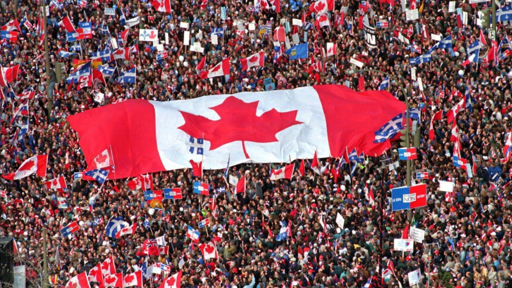 "In this Friday, Oct. 27, 1995 file picture, a large Canadian flag is passed through a crowd in as thousands streamed into Montreal from all over Canada to join Quebecers rallying for national unity three days before a referendum that could propel Quebec toward secession. Even if Quebec voters had said ""Oui"" to independence in 1995, the United States wasn't going to say ""Yes"" to immediately recognizing the new country or including it in the North American Free Trade Agreement. THE CANADIAN PRESS/Ryan Remiorz"
