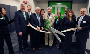 Annalisa Russell-Smith |    Using a ribbon made from real bank notes, New Britain Mayor, Tim O'Brien, center, officially opens the new offices of TD Bank at 178 Main Street Thursday. TD Bank executives from left, Ale Federico, Michael LaBella, John Cookley, Mauro DeCarolis, Kelly McBride, O'Brien, Diane Eschner, Carl Hinds, Sheila Amaral and Bill Carroll of the Greater New Britain Chamber of Commerce.