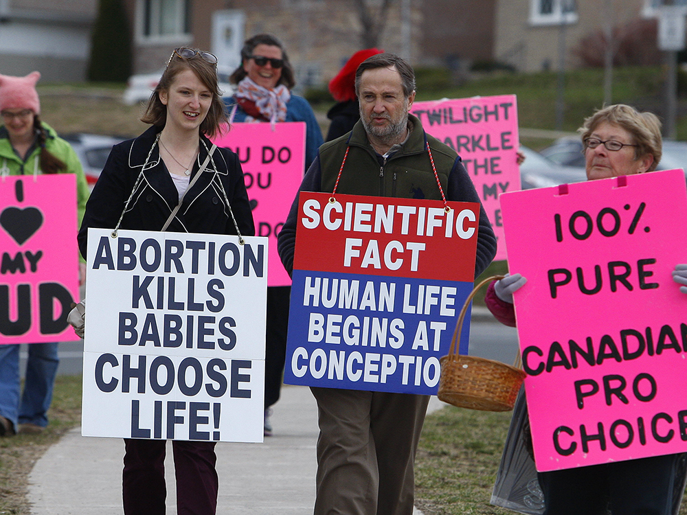 Pro-choice group Love Team Peterborough march carrying bright pink signs alongside the Peterborough Pro-Life group outside Peterborough Regional Health Centre (PRHC) on Saturday April 15, 2017 in Peterborough, Ont. Love Team Peterborough was formed in December. Crystal Mosey, a respite-care worker, started the group with two of her friends. Every Saturday morning since Dec. 10, they've gone to PRHC with signs voicing their concerns. CLIFFORD SKARSTEDT/PETERBOROUGH EXAMINER/POSTMEDIA NETWORK
