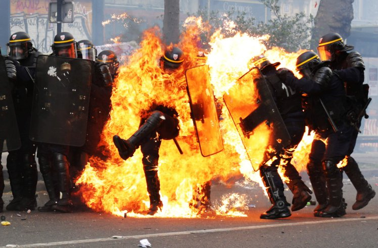 French CRS anti-riot police officers are engulfed in flames as they face protesters during a march for the annual May Day workers' rally in Paris on May 1, 2017. / AFP PHOTO / Zakaria ABDELKAFIZAKARIA ABDELKAFI/AFP/Getty Images