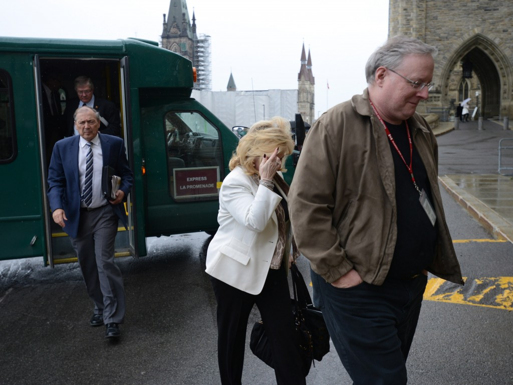 An unidentified man shields Sen. Pamela Wallin from media cameras as she arrives at the Senate entrance on Parliament Hill in Ottawa, Thursday, June 6, 2013. THE CANADIAN PRESS/Sean Kilpatrick